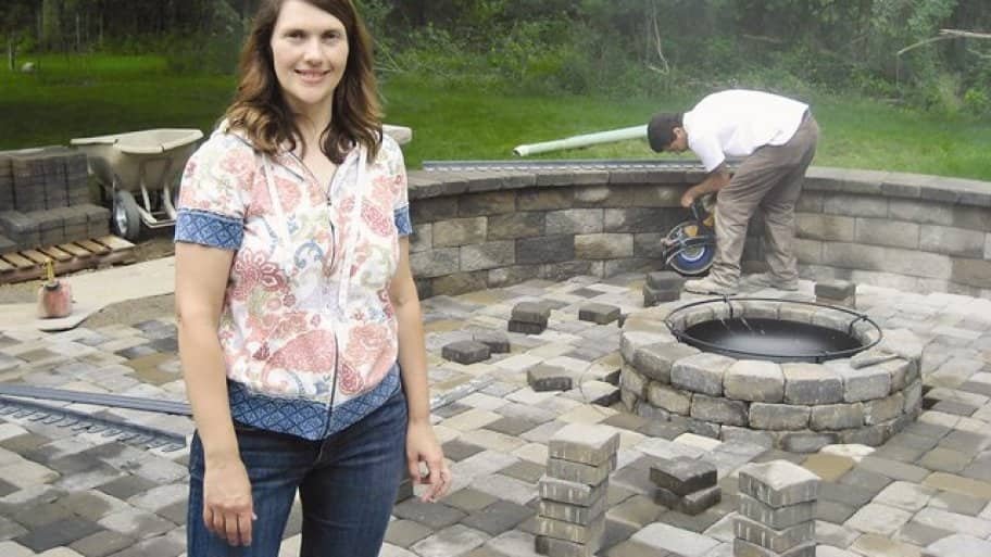 homeowner stands on new paver patio
