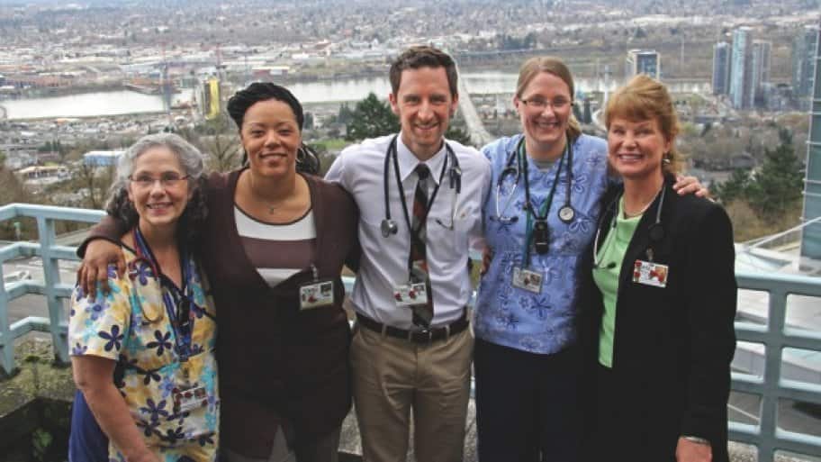 a male doctor and his female medical team posed on a balcony with a view of the city of Portland below.