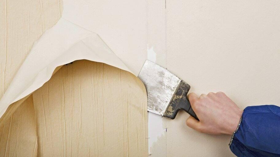 a scraper removing wallpaper
